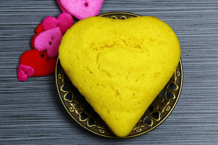 Top view of Brazilian corn bread in the shape of a heart on a plate Imagens
