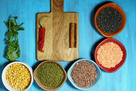 mung: Different kinds of Indian lentils in colorful bowls with spices and cilantro on a blue wooden background