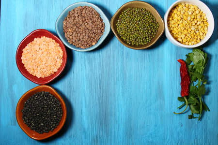 mung: Different kinds of Indian lentils in colorful bowls on a blue wooden background with copy space