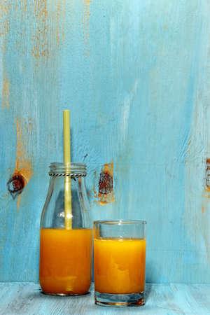 青い木製の背景のオレンジ ジュース