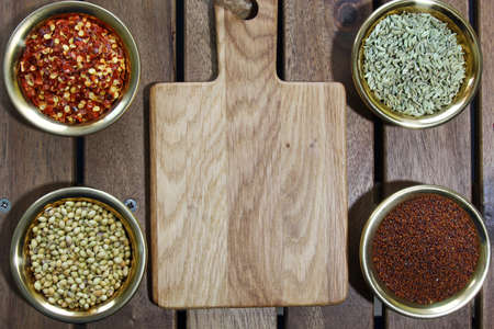 nigella seeds: Bowls of spices containing mustard seeds, fennel seeds, coriander seeds, red pepper flakes on a wooden background sith copy space.Top view. Stock Photo