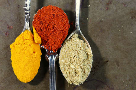 Spoonful of yellow Turmeric, red paprika  and coriander powder with copy space on rustic background, selective focus.