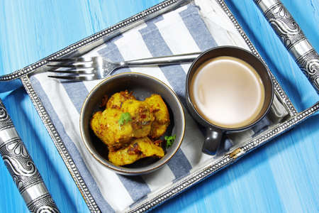 Overhead view of dry Gatte ki sabji or Dhoka made of chickpea flour or Besan with onions and ginger and other Indian spices and a cup of tea on a metal tray on blue wooden background.