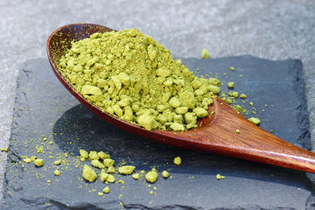 Green Matcha powder in a spoon on a slate colored tile Stock Photo - 79743971