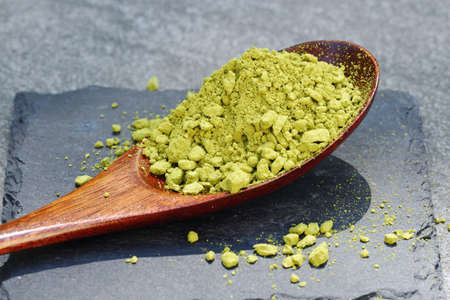 Green Matcha powder in a spoon on a slate colored tile Stock Photo - 79744121