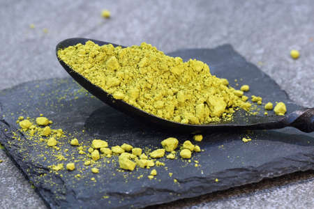 Green Matcha powder in a spoon on a slate colored tile, selective focus Stock Photo - 79744129