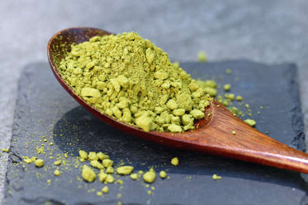 Green Matcha powder in a spoon on a slate colored tile, selective focus.