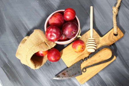 Overhead shot of Red Cherry plums on grey background Stock Photo