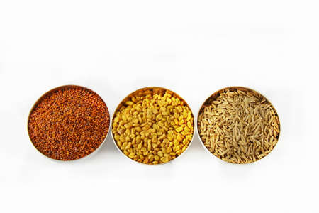 Three steel bowls with cumin fenugreek seeds, cumin seeds and mustard seeds on white