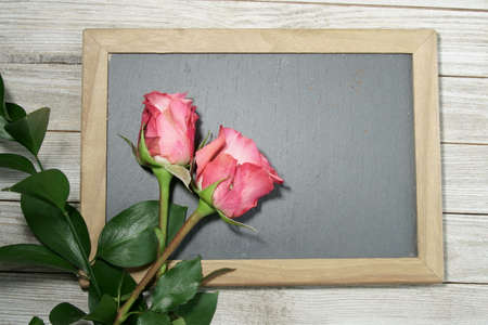 Pink Roses on a grey slate with copy space for a message. Stock Photo
