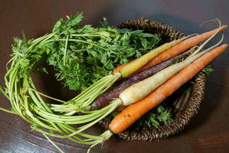 Rainbow colored organic Carrots on a wooden background.