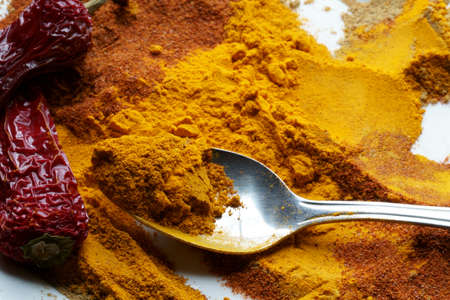Close up of Indian spices of Turmeric powder, coriander powder and chili powder on a plate with a spoon.