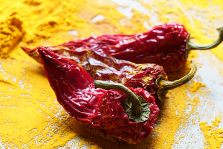 Close up of red Chiili peppers on Turmeric powder