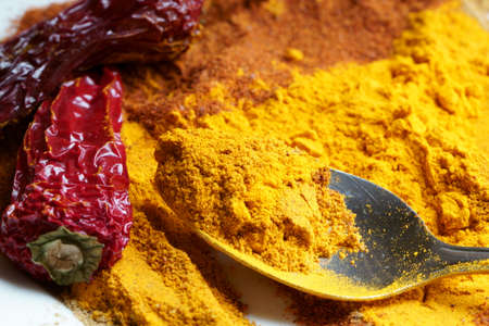 Close up of Indian spiceTurmeric powder in a spoon. Stock Photo