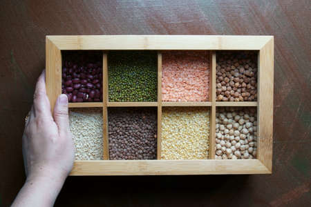 A hand with a box of different kinds of lentils, a great source of protein.