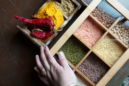 A hand holding a box with different kinds of lentils and beans and a spices wooden box. Stock Photo