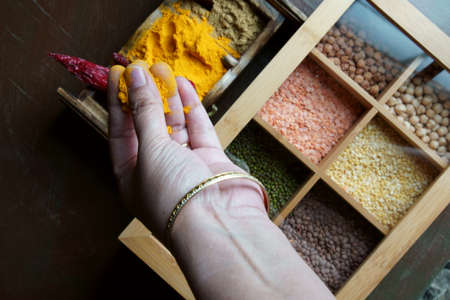 Top down view of a hand with a pinch of Turmeric from a spices box. Stock Photo