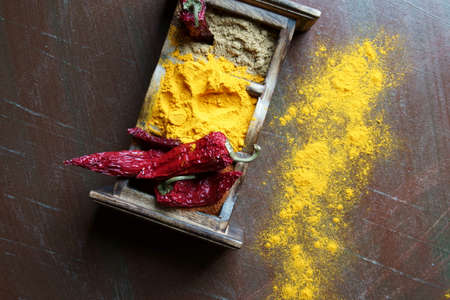 Close up of Indian spices of Turmeric powder, coriander powder and chili powder in  a wooden box with a spoon. Stock Photo