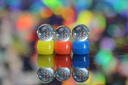 Three transparent marble shaped balls with colorful background