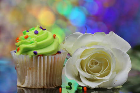 Three cup cakes with selective focus and a colorful bokeh.