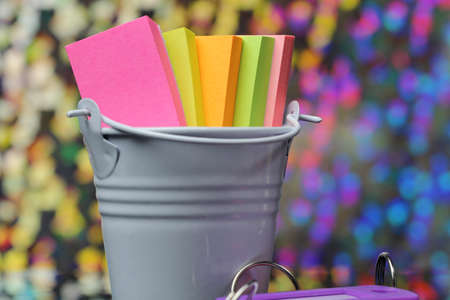 A container with colorful sticky notes.