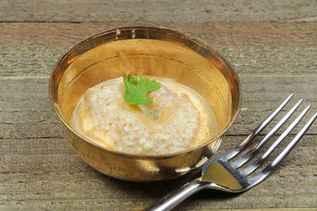 Dahi Vada, an Indian snack made of deep fried lentil dumplings soaked in yogurt sauce. Stock Photo