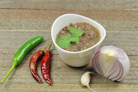 Vegan spicy whole black lentils or urad daal on a wooden background. Stock Photo