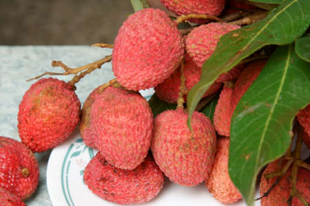 A bunch of red Lychees with copy space. Stock Photo