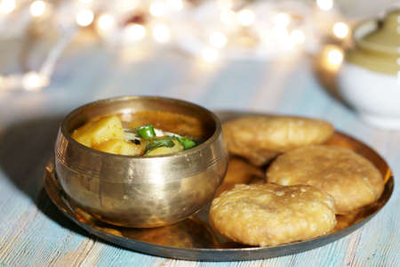 A plate of Khasta Kachauri with a bowl of spicy and tangy Potato sabji or curry.