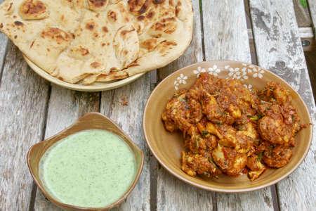 Top down veiw of  homemade Tava Chicken with green raita chutney and Tandoori Roti