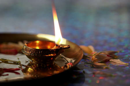 A close up of Oil lamps with flower petals,  for a Hindu festival Diwali, selective focus.