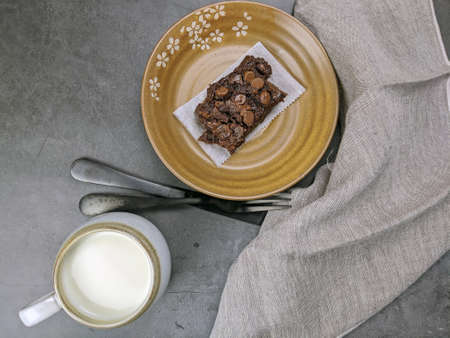 Homemade Chewvy Brownie with a cup of milk and copy space. Stock Photo