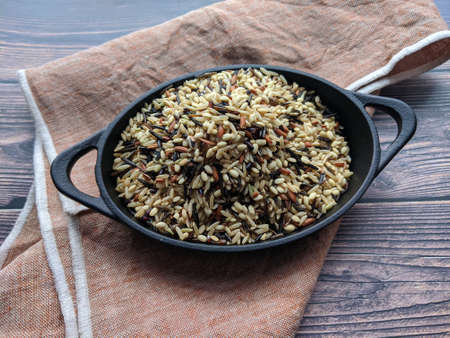 Overhead view of a mini pot of cast iron with Wild Rice with copy space.