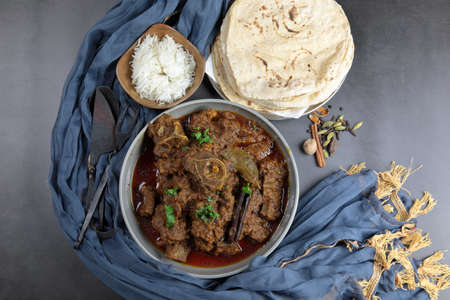 Overhead view of Goat curry, Mutton curry, Nihari, Rogan Josh in a bowl with Chapati and plain Rice with copy space. Banco de Imagens