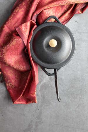 Overhead view of empty cast iron mini pot with napkin and copy space. Banco de Imagens