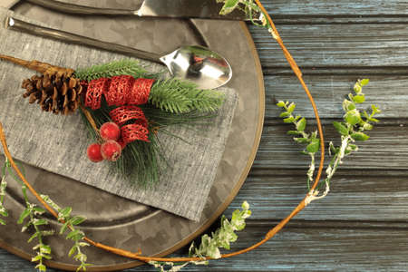 Overhead view of  table setting - a plate with spoon, fork and knife with a Christmas decoration on a wooden background.