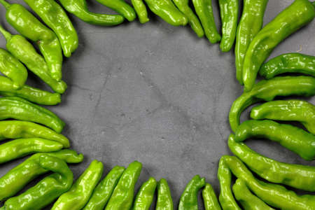 Green Shishito peppers in a circle with an empty space in the center for copy space.