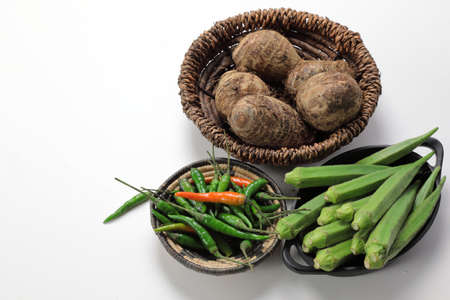 Indian vegetables of Yams or Taro root , Ladys finger or Okra and green chilies wooden background with copy space.