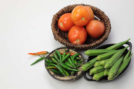 Indian vegetables of Tomatoes,ladys fingers and green chilies  on wooden background with copy space.