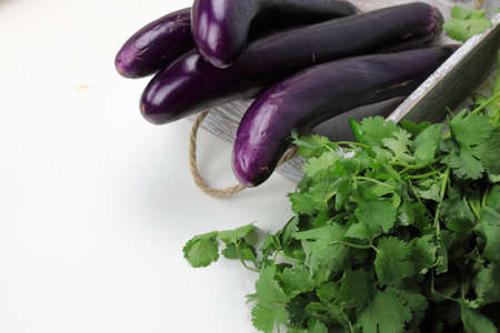 A container with long purple Chinese Eggplants or Brinjal on wooden background with copy space.
