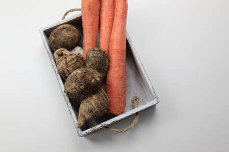 Carrots and Yams in a wooden tray on wooden white background with copy space. Stock Photo