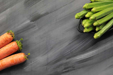 A wooden grey background with Carrots and Okra as border with copy space.