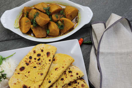 Homemade Indian vegetarian food of Yam or Taroo root curry with gluten free Besan Roti or Chickpea flour Roti on a wooden background.
