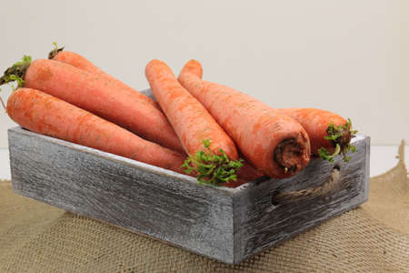 A stack of orange Carrots on a wooden background with accomodation for copy space. 写真素材
