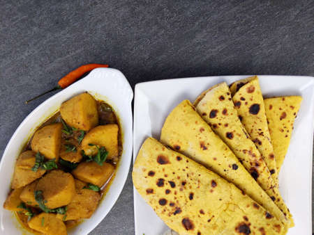 Homemade Indian vegetarian food of Yam or Taro root curry with gluten free Besan Roti or Chickpea flour Roti on a wooden background.