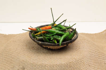 A small basket with Green Thai chili peppers on wooden background with copy space.