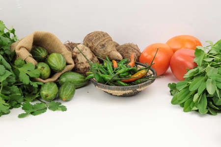 Indian vegetables of Tomatoes, carrots, Yams, Pointed gourd, Green chilies, Methi leaves, cilantro, and egg plants on wooden background with copy space.