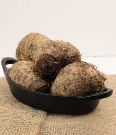 A conatiner with Taro roots or Colocasia or yams with accomodation for copy space. Stock Photo