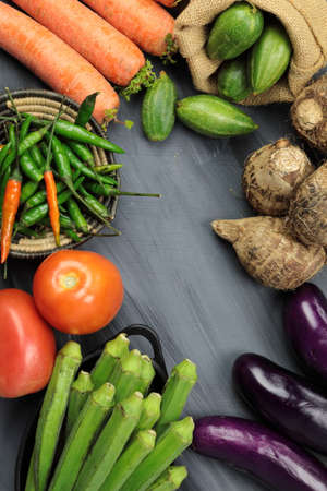 Top down view of  Indian vegetables of Tomatoes, carrots, Yams, Pointed gourd, Green chilies, Methi leaves, cilantro, and egg plants on wooden background with copy space.