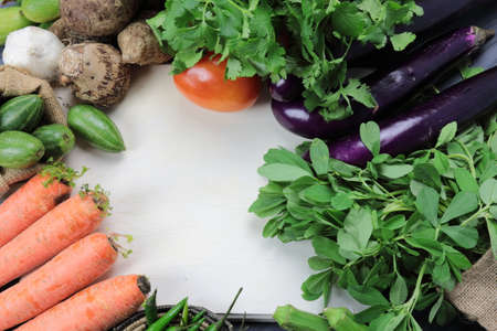 Top down view Indian vegetables of Tomatoes, carrots, Yams, Pointed gourd, Green chilies, Methi leaves, cilantro, and egg plants on wooden background with copy space. Stock Photo